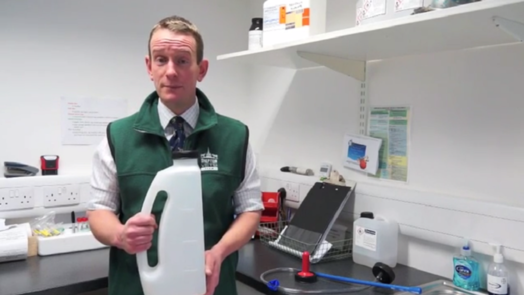 Image of a vet holding a plastic jug in a vet consult room